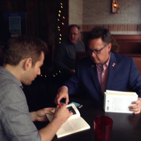 Chad Kimball, who portrays Kevin Tuerff in Come From Away autographs copies of Channel of Peace.